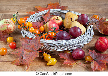 Autumn still life. Various fruits and autumn leaves are lying in a wicker basket.