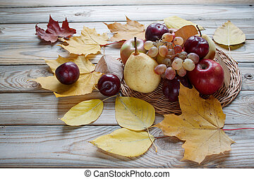 Autumn still life. Various fruits are lying in the wicker plate and the wooden desk. Autumn yellow leaves.