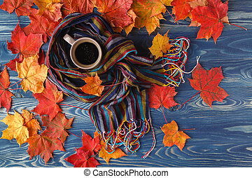 Autumn still life - Warm knitted scarf and cup of coffee on rustic wooden table with colorful fall maple leaves
