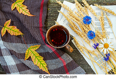 Autumn still life with a cup of tea, ears of wheat, cornflowers, a warming scarf and colorful leaves
