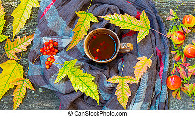 Autumn still life with cup of tea, warming scarf and colorful leaves over rustic wooden background