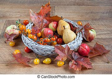 Autumn still life with fruits and autumn leaves are lying in a wicker basket.