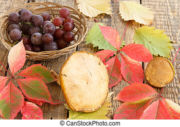 Autumn still life with mushrooms, grapes in wicker basket, green and red leaves