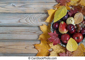 Autumn still life with various fruits are lying in a wicker basket. Autumn maple and poplar leaves.