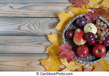 Autumn still life with various fruits are lying in a wicker basket. Autumn maple leaves.