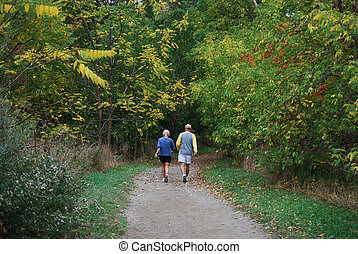 Autumn Stroll - older couple stroll through park