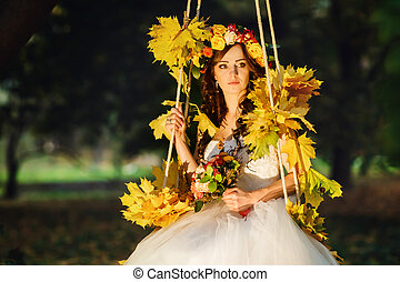 Autumn sun shines over s stunning bride while she sits on a swing