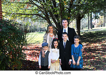 Family of six poses besides their home on a Sunday morning. They are dressed up in suits and dresses. All are smiling and happy.