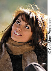 Autumn sunlight - Young woman smiling, looking up, sunlight...