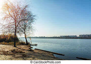 Autumn sunny landscape. Beach with a pier near the river -...