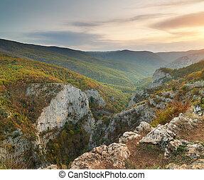 Autumn sunset in mountain canyon.