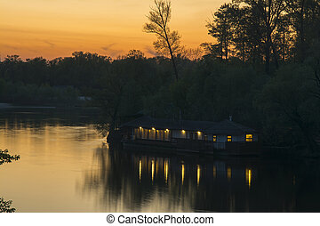 Autumn sunset on the river among the trees
