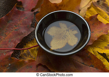 Autumn tea ceremony still life black cup of tea closup background