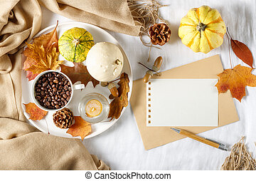 Autumn Thanksgiving holiday mockup.  Composition with pumpkins, fallen leaves, cup of coffee beans, beige cashmere scarf  on linen