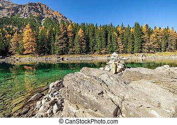 Autumn time at romantic mountain lake with stone cairns in foreground. Lake Obernberg, Stubai Alps, Tyrol, Austria.