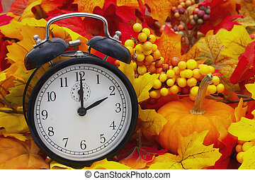 Autumn Time Change, Autumn Leaves and Alarm Clock with a pumpkin