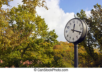 Autumn Time is eighteen minutes in the afternoon concept. Big clock in autumn city park landscape