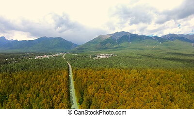 Autumn. Transition from summer to fall. Aerial shot of forest and mountains