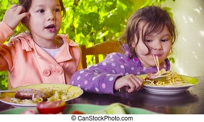 Two naughty girls are sitting at the table and eating pasta...