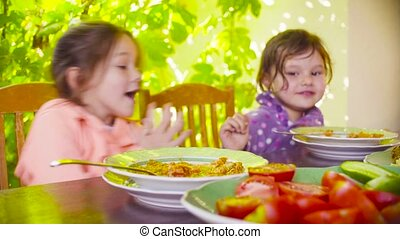 Two naughty girls are sitting at the table and eating soup -...