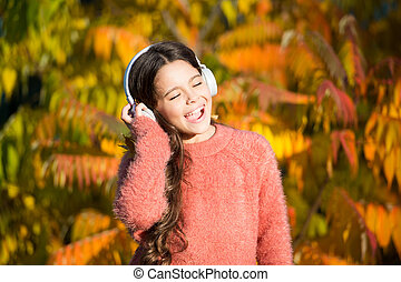 Autumn walks with nice songs. Music for autumn mood. Listening song. Enjoy music fall day. Listening audio best way help child improve vocabulary. Kid girl relaxing near autumn tree with headphones