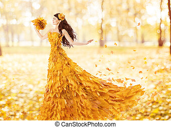 Autumn woman in fashion dress of fall maple leaves artistic