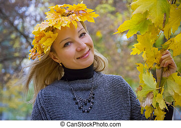 Autumn woman with yellow maple leaves
