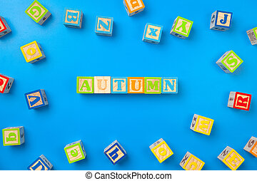 Autumn. Wooden colorful alphabet blocks on blue background, flat lay, top view.