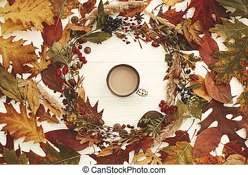 Autumn Wreath Flat Lay. Coffee in Fall leaves circle with berries, nuts, acorns, flowers,herbs on rustic white background top view. Seasons greetings. Space for text. Cozy Autumn image