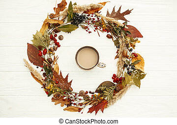 Autumn Wreath Flat Lay. Coffee in Fall leaves circle with berries, nuts, acorns, flowers,herbs on rustic white background top view. Seasons greetings. Space for text. Autumn mockup card