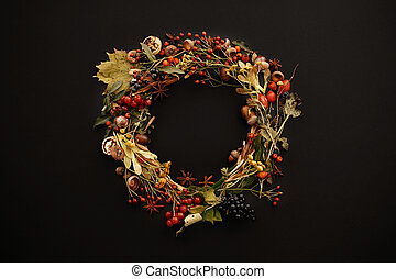 Autumn Wreath Flat Lay. Fall leaves circle with berries, nuts, acorns, flowers,herbs on black background top view. Seasons greetings. Space for text. Autumn mockup card.