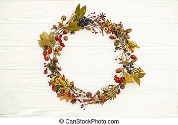 Autumn Wreath Flat Lay. Fall leaves in circle with berries,nuts,acorns,flowers,herbs  on rustic white background top view. Seasons greetings. Space for text. Autumn mockup card