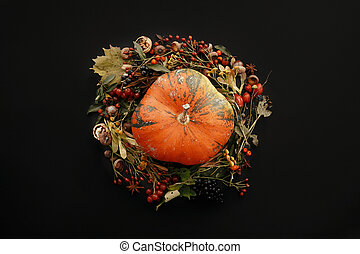 Autumn Wreath Flat Lay. Pumpkin in Fall leaves circle with berries, nuts, acorns, flowers,herbs on black background top view. Seasons greetings. Space for text. Autumn mockup card