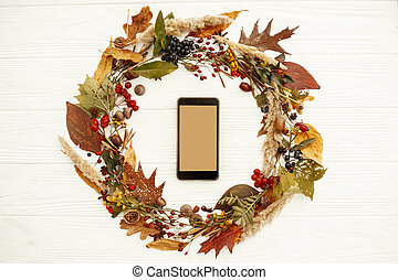 Autumn Wreath Flat Lay with phone. Empty screen smartphone in fall leaves circle with berries, nuts, acorns, flowers on black background top view. Seasons greetings. Space for text