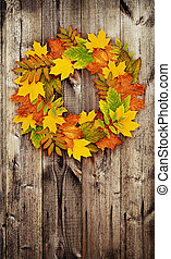 Autumn wreath from colored dry leaves on door