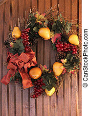 Autumn Wreath - Wreath in autumn colors hanging on wood...