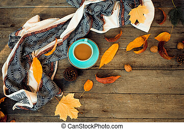 Autumn yellow leaves, a blue cup of coffee and clothes on a wooden background.