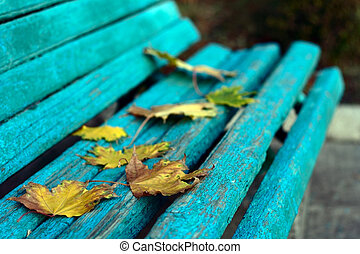 autumn begining yellow leaves on blue old bench