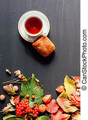 autumn yellow leaves Tea Cup cake on black background