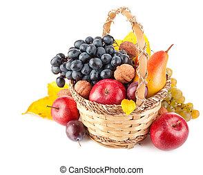 autumnal fruit in basket isolated on white background