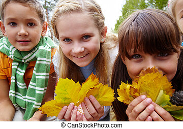 Portrait of two girls with yellow leaves peeking out of them on background of cute boy