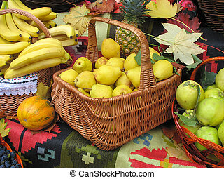 autumnal harvest fruit in basket over carpet and leaves