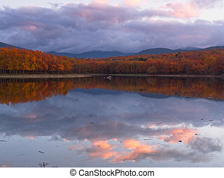 Autumnal landscape with reflections in the water of the clouds at dusk