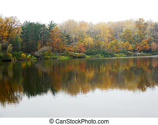 Autumnal landscape with tranquil river, bank, trees, forest, reflection, haze