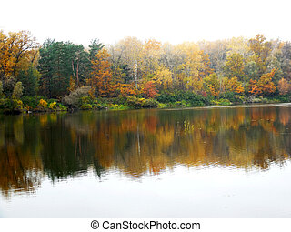 Autumnal landscape with tranquil river, trees, forest, reflaction, haze