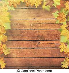 Autumnal leaves over old wooden desk, seasonal backgrounds