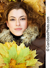 close-up portrait of young woman with yellow leaves