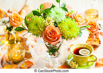 Autumnal table setting with bunch of autumn flowers and cup...