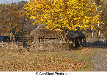 Autumnal view. Ukrainian hut with thatched roof. Wattle....