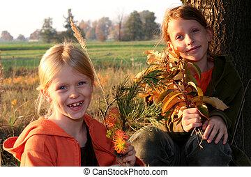 Autumnal walk  - Two girls sitting under the tree